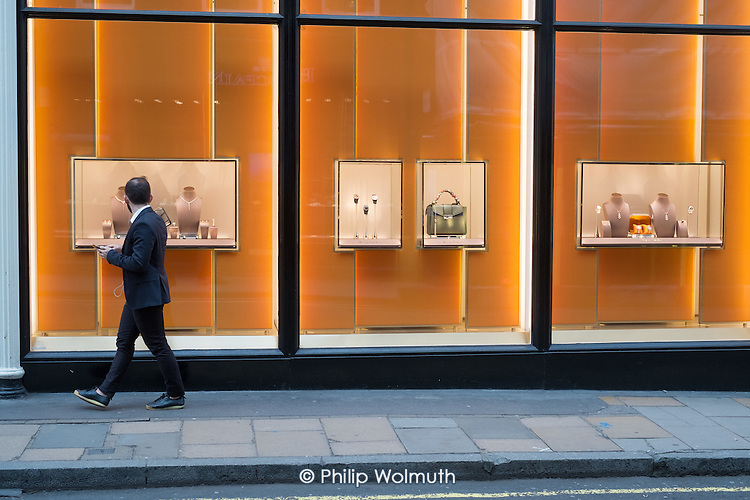 Window shopper outside Bulgari luxury goods shop, Mayfair, London.