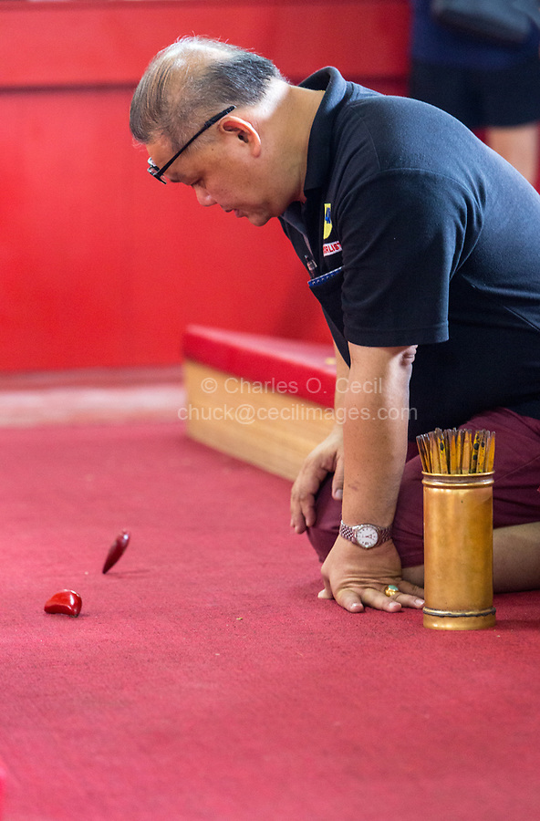 George Town, Penang, Malaysia.  Worshiper Using Jiaobei Blocks to Seek Direction from the Gods, Goddess of Mercy Temple, Kuan Yin Teng, Kong Hock Keong.  Cannister of Fortune Sticks by his Knee.