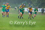 Kerry's Rachel McCarthy in possession as Clare's Sarah Ní Ceallaigh watches during a downpour in the Munster Junior Camogie final