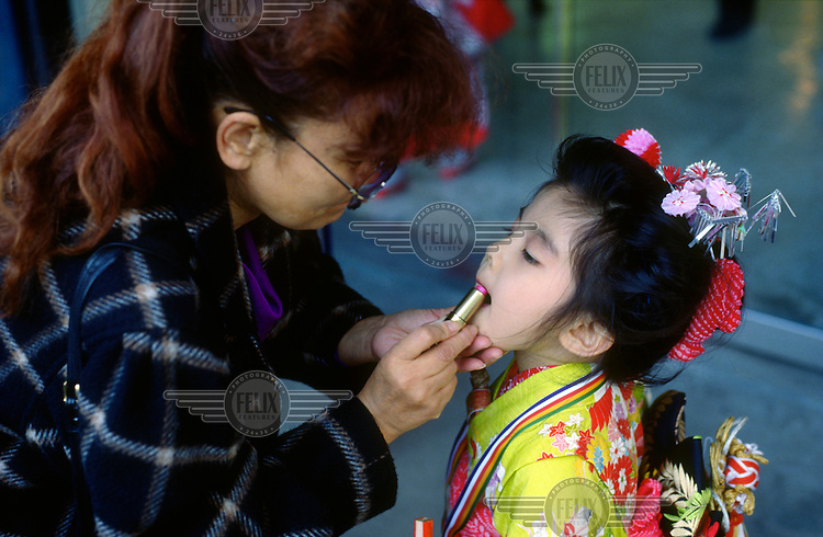 A mother fixes her daughter's make up at the annual Shichigosan (meaning 'Seven Five Three') festival. During the festival, girls, aged three and seven, and boys, aged three and five, are brought to the Shinto shrines for prayers to ensure good health and growth.