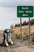 """A roadsign along Intersate 80 In Nevada pointing the way to """"Deeth"""" and """"Starr Valley"""" has been combined in photo software with a toy R2D2 robot."""