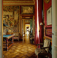 In the billiard room golden parquet floors glow against warm red walls and an antique tapestry
