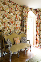 An Indian sofa occupies one fabric-covered wall of this turret bedroom