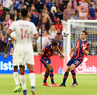 AUSTIN, TX - JULY 29: Reggie Cannon #2 of the United States heads the ball up the field in front of James Sands #16 of the United States during a game between Qatar and USMNT at Q2 Stadium on July 29, 2021 in Austin, Texas.