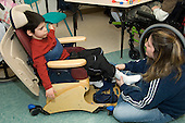 MR / Albany, NY.Langan School at Center for Disability Services .Ungraded private school which serves individuals with multiple disabilities.A mother visiting the classroom puts on her son's AFO (Ankle foot orthotic) Boy: 8, cerebral palsy, spastic quadriplegic, nonverbal with expressive and receptive language delays.MR: Hac2 , Ble1.© Ellen B. Senisi