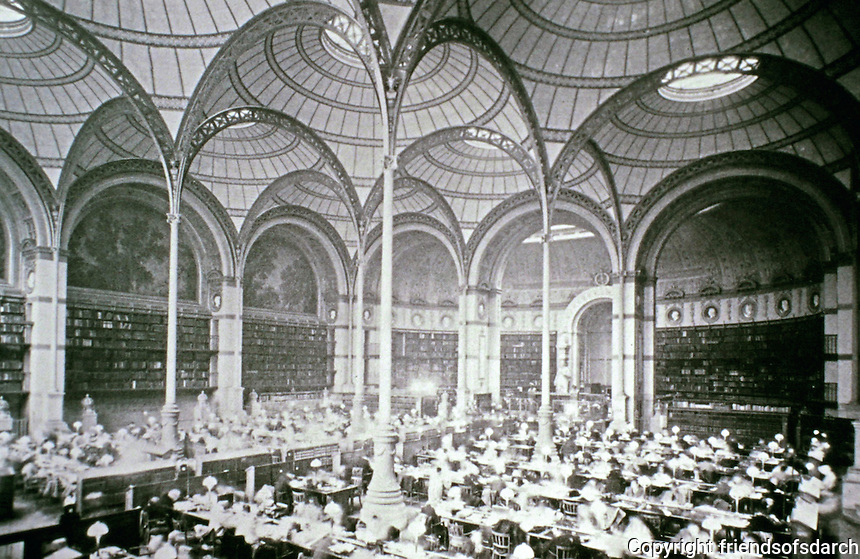 Reading room of the Bibliothèque Nationale (1859–75),  designed by Architect Henri Labrouste. Features included the use of exposed metal frameworks, thin masonry walls, domed roof, glass skylights that diffuse natural sunlight onto lustrous ceramic panels, slender iron columns. Historical photo.