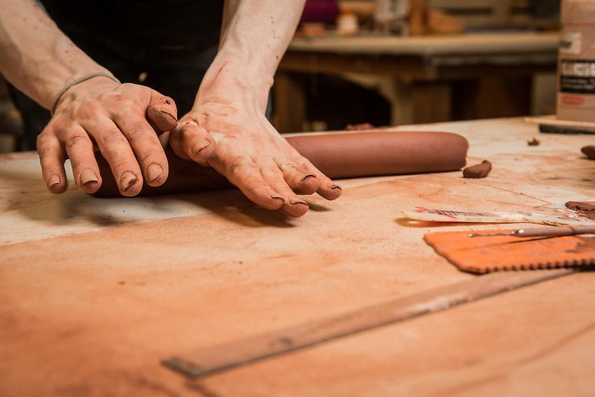 Brian Adams works on a clay sculpture during  Intermediate Handbuilt Ceramics (ART A301) in UAA's fine arts building.