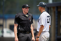 GCL Yankees East coach Dan Fiorito (27) talks with umpire Jacob McConnell during a Gulf Coast League game against the GCL Phillies East on July 31, 2019 at Yankees Minor League Complex in Tampa, Florida.  GCL Phillies East defeated the GCL Yankees East 4-3 in the second game of a doubleheader.  (Mike Janes/Four Seam Images)