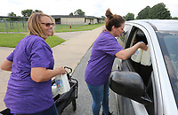 Alice Higgs (left), cafeteria manager at Elkins Elementary School, and Laura Srader (cq), cafeteria manager at Elkins Primary School, places Monday, July 19, 2021, milk and other school meal items in a car during the Elkins School District Free Summer Meals Program distributed on Mondays at the Primary School in Elkins. The weekly meal program includes seven breakfasts and seven lunches and will end this coming Monday July 26. The meals can be picked up from 8:00 a.m. to 1:00 p.m.. Check out nwaonline.com/210720Daily/ and nwadg.com/photos for a photo gallery.(NWA Democrat-Gazette/David Gottschalk)