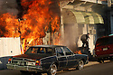 A Treme resident flees his home as a fire rages next door. The fire is one of several  in the area that firemen suspect of arson during the past two weeks, New Orleans, Jan. 27, 2004.