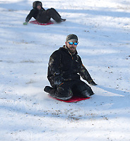 Andrew Newton (center) of Prairie Grove reaches to steady himself Friday, Feb. 19, 2021, as he leads his son, Gabe Newton, 9, downhill on storage container lids while sledding at Battlefield State Park in Prairie Grove. The Newtons were taking a break from virtual instruction to take advantage of the good sledding conditions before warm temperatures melted the snow from the hillside. Visit nwaonline.com/210220Daily/ for today's photo gallery. <br /> (NWA Democrat-Gazette/Andy Shupe)