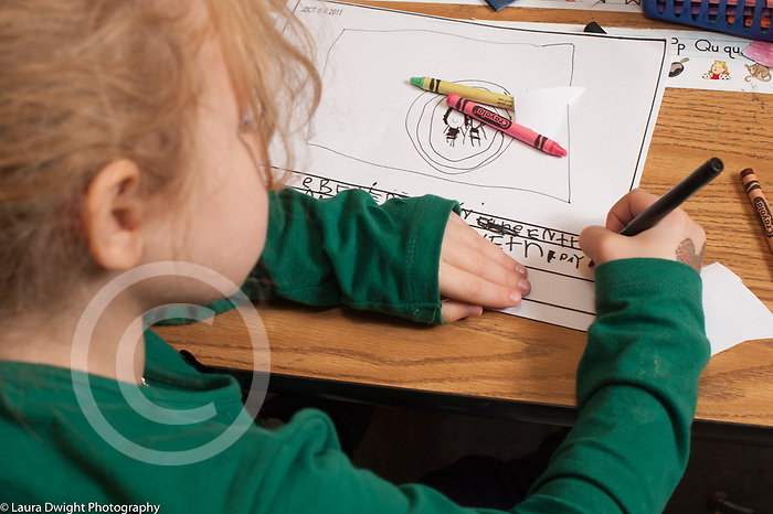 Education Elementary public school Kindergarten girl writing on bottom of drawing or page of story