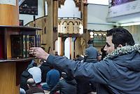 Freitagsgebet in der Dar Assalam Moschee in Berlin-Neukoelln.<br /> Im Bild: Ein Glaeubiger nimmt sich vor dem Gottesdienst ein Exemplar des Koran.<br /> 26.2.2016, Berlin<br /> Copyright: Christian-Ditsch.de<br /> [Inhaltsveraendernde Manipulation des Fotos nur nach ausdruecklicher Genehmigung des Fotografen. Vereinbarungen ueber Abtretung von Persoenlichkeitsrechten/Model Release der abgebildeten Person/Personen liegen nicht vor. NO MODEL RELEASE! Nur fuer Redaktionelle Zwecke. Don't publish without copyright Christian-Ditsch.de, Veroeffentlichung nur mit Fotografennennung, sowie gegen Honorar, MwSt. und Beleg. Konto: I N G - D i B a, IBAN DE58500105175400192269, BIC INGDDEFFXXX, Kontakt: post@christian-ditsch.de<br /> Bei der Bearbeitung der Dateiinformationen darf die Urheberkennzeichnung in den EXIF- und  IPTC-Daten nicht entfernt werden, diese sind in digitalen Medien nach §95c UrhG rechtlich geschuetzt. Der Urhebervermerk wird gemaess §13 UrhG verlangt.]