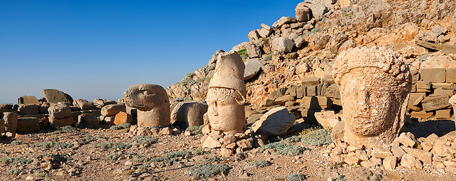 Statue heads, from right, Commagene, Antiochus, & Eagle, with headless seated statues in front of the stone pyramid 62 BC Royal Tomb of King Antiochus I Theos of Commagene, east Terrace, Mount Nemrut or Nemrud Dagi summit, near Adıyaman, Turkey