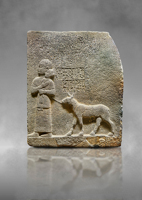 """Hittite monumental relief sculpted orthostat stone panel of Royal Buttress. Basalt, Karkamıs, (Kargamıs), Carchemish (Karkemish), 900-700 B.C. Anatolian Civilisations Museum, Ankara, Turkey<br /> <br /> The queen carries her youngest son. The hieroglyphs located above read; """"and this is Tuwarsais; the prince desired by the ruler, whose exclusiveness has been exposed"""". While the queen carries her son in her lap, she holds the rope of the colt coming behind with her other hand. The muscles of the colt are schematic. <br /> <br /> Against a grey art background."""
