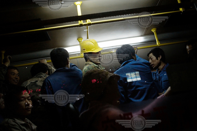 Migrant workers from construction sites join other city commuters on a bus at the end of the day. The workers head back to their temporary accommodation.