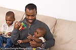 2 year old toddler boy shaking toy for 5 month old baby brother, held by father African American horizontal