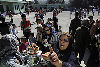 Pictured: Army officers hand over food to the hundreds of refugees Friday 26 February 2016<br />Re: Hundreds of refugees have been given temporary shelter at the Stefanakis Army Camp in the Schisto area of Athens, Greece.