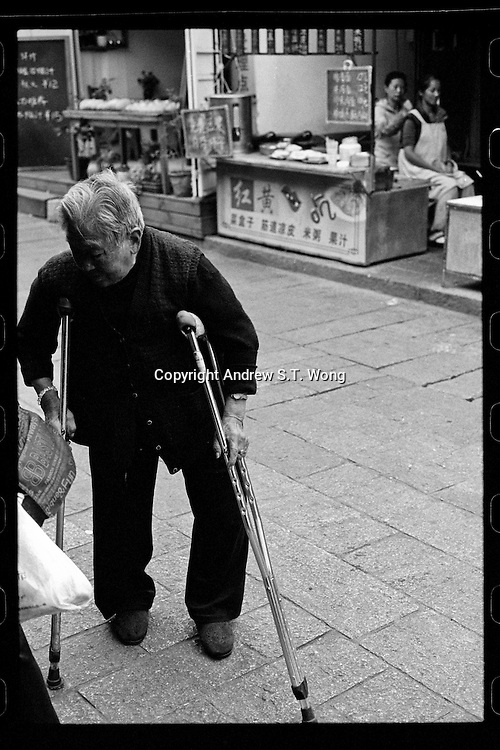An elderly woman on crutches talks through an old street against a backdrop of a vendor receiving massage at a shop in the ancient city of Dali, Yunnan province, China, October 2013.