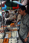 Bengali sweets selling at a street food stall  in Dalhousie area of Kolkata. Street food stalls are serving the office goers for decades. All kind of Indian foods are available on the street at an affordable price. They sale them openly. Street food stalls are another results of unempoloyment and over poppulation. They serve millions of people in India. Kolkata, West Bengal,  India  7/18/2007.  Arindam Mukherjee/Landov