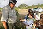 Ethan Kuhlken holding a wild female cardinal to release it after it was banded at Guadalupe River State Park during Park Interpreter Craig Hensley's Bird in the Hand educational bird banding event.