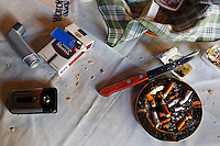 A knife, an ash tray filled with used cigarettes, a mobile phone, a lighter, a box of cigarettes and an inhaler on a table at a restaurant in the El Caminito area of Buenos Aires.