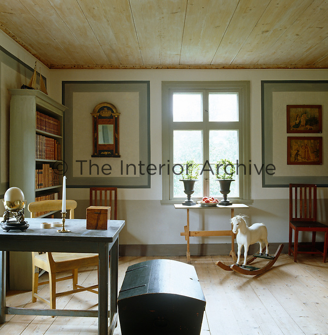 This simple study is decorated with painted panels on the walls and a few items of painted furniture
