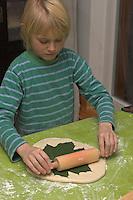 Kinder basteln Blattkacheln aus Salzteig, Junge macht einen Abdruck von einem Ahornblatt auf den Salzteig
