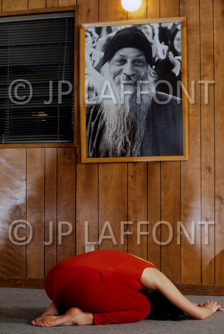 Wasco, Oregon, February 1984: A disciple meditating under the portrait of Bhagwan Rajneesh hanging on the wall. Rajneeshpuram, was an intentional community in Wasco County, Oregon, briefly incorporated as a city in the 1980s, which was populated with followers of the spiritual teacher Osho, then known as Bhagwan Shree Rajneesh. The community was developed by turning a ranch from an empty rural property into a city complete with typical urban infrastructure, with population of about 7000 followers.