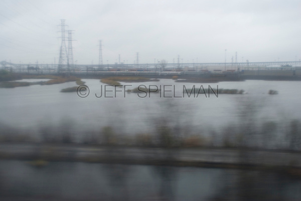 Industrial Area in the New Jersey Meadowlands viewed from the window of a moving passenger train, New Jersy, USA....Another Commuter Train is Visible in the Distance