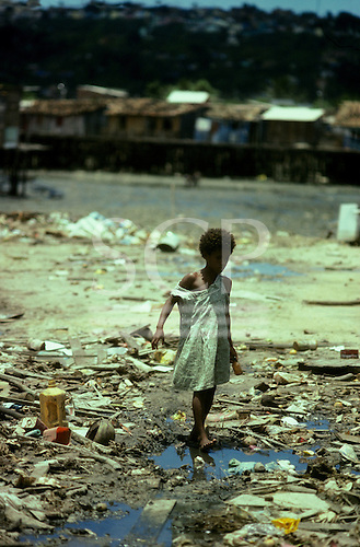 Salvador, Brazil. Young girl picking her way through the filth and rubbish of the shore; Alagardos, Bahia State.