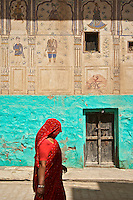 Women walking in Mandawa Founded in the 18th century, the medieval fort of Mandawa dominates the town with a painted arched gateway adorned with Lord Krishna and his cows. The Chokhani and Ladia havelis and the street with Saraf havelis are some of the splendid examples of this region's havelis..The Binsidhar Newatia Haveli has some curious paintings on its outer eastern wall-a boy using a telephone, and a European woman in a car driven by a chauffeur. The Gulab Rai Ladia Haveli has some defaced erotic images..Rajasthan India,