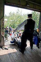 The conductor helps returning campers and hikers load their gear at the Spencer Glacier Whistle Stop.
