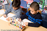 Education Preschool 4-5 year olds art activty two boys drawing with markers side by side horizontal