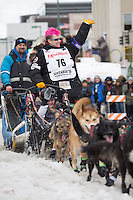 Heidi Sutter and team leave the ceremonial start line with an Iditarider at 4th Avenue and D street in downtown Anchorage, Alaska during the 2015 Iditarod race. Photo by Jim Kohl/IditarodPhotos.com