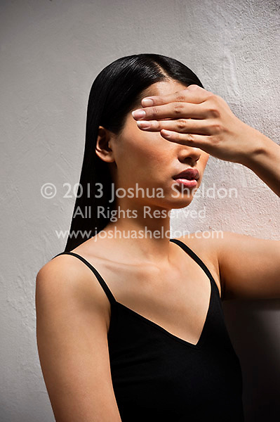 Asian woman covering her eyes with her hand