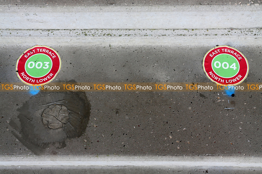 Numbered markers on the terracing to indicate standing positions during Stevenage vs Swansea City, Emirates FA Cup Football at the Lamex Stadium on 9th January 2021