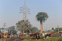 INDIA Dhanbad, coal mining of BCCL Ltd a company of COAL INDIA, a village which will be displaced by coal mining, old chimney with growing tree and steel lattice tower  / INDIEN Dhanbad , Kohleabbau von BCCL Ltd. ein Tochterunternehmen von Coal India, ein Dorf das durch den Kohletagebau umgesiedelt werden muss, aus einem alten Schornstein waechst ein Baum