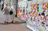 Two Sikhs in traditional dress walk past posters advertising an Asian music festival in Forest Gate, London.