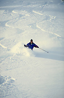 A lone skier cuts down an open slope of waist deep powder. Senior citizen. Darrell Rikli. Utah, Alta Ski Resort.