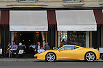 Waiter looking at yellow Ferrari sports car parked in front of a restaurant, Paris, France.