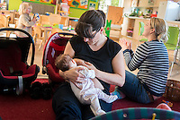 A mother breastfeeds her young baby at a drop-in breastfeeding support centre, while another mum plays with a toddler in the background.<br /> <br /> Hampshire, England, UK<br /> 05/03/2014<br /> <br /> © Paul Carter / wdiip.co.uk