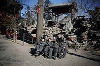 CHINA. Security guards taking a break during Chinese New Year in Baiyun Temple in Beijing.  Chinese New Year, or Spring Festival, is the most important festival and holiday in the Chinese calendar In mainland China, many people use this holiday to visit family and friends and also visit local temples to offer prayers to their ancestors. The roots of Chinese New Year lie in combined influences from Buddhism, Taoism, Confucianism, and folk religions.  2008.