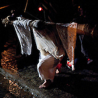 A man attached to a cross prays at one of the 14 stations of the cross or 'Via Crucis', a depiction of the final hours of Jesus Christ during the Holy Week procession of the 'Empalaos' in Valverde de la Vera, on April 6, 2012. Empalaos make the steps of the 'Via Crucis', marking the Stations of the Cross, during the night of Maundy Thursday while bound by rope to a crucifix as an act of penance and to honour a promise made to the Empalaos Brotherhood and the Christ of Vera Cruz, in the town of Valverde de la Vera. The process of dressing the Empalao in the traditional costume is taken with great care, with the family and dressers paying attention to ensure that no harm is caused to the penitent and that they are aided in their recovery, including being massaged and rubbed with rosemary alcohol. Many Spanish towns and villages retain such rites and religious traditions, many passed down from medieval times, across the Easter weekend. (c) Pedro ARMESTRE