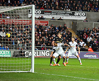 Wednesday, 01 January 2014<br /> Pictured: Ashley Williams of Swansea (2nd L) fails to score with a header from a cross, after Joe Hart, Manchester City goalkeeper (not pictured) fails to save the ball.<br /> Re: Barclay's Premier League, Swansea City FC v Manchester City at the Liberty Stadium, south Wales.