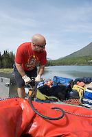 Nick Lynch pumps up his raft at Cooper Landing along the Kenai River.