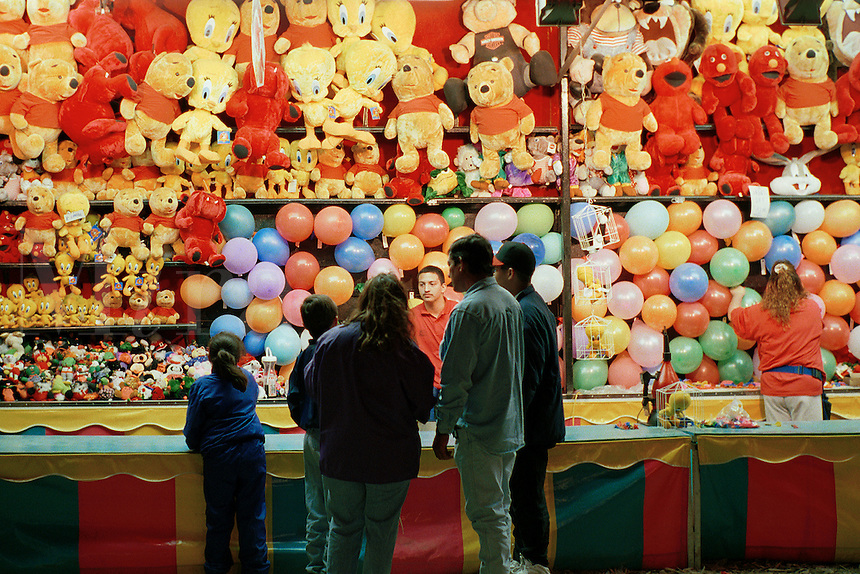 Carnival midway at annual Jalapeno festival near the Texas Mexico border. Stuffed animals. Dart toss game. Laredo Texas.