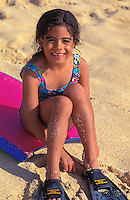 Little girl smiling and playing with a boogieboard and flippers on the beach at the north shore