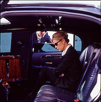 Man looking through limousine window at woman executive