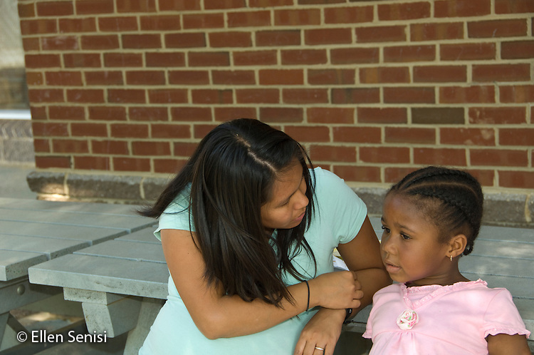 MR / College Park, Maryland.Center for Young Children, laboratory school within the College of Education at the University of Maryland. Full day developmental program of early childhood education for children of faculty, staff, and students at the university..Student (girl, 5, African American) talks with teacher outside during recess..MR: Fow1 Smi26.© Ellen B. Senisi